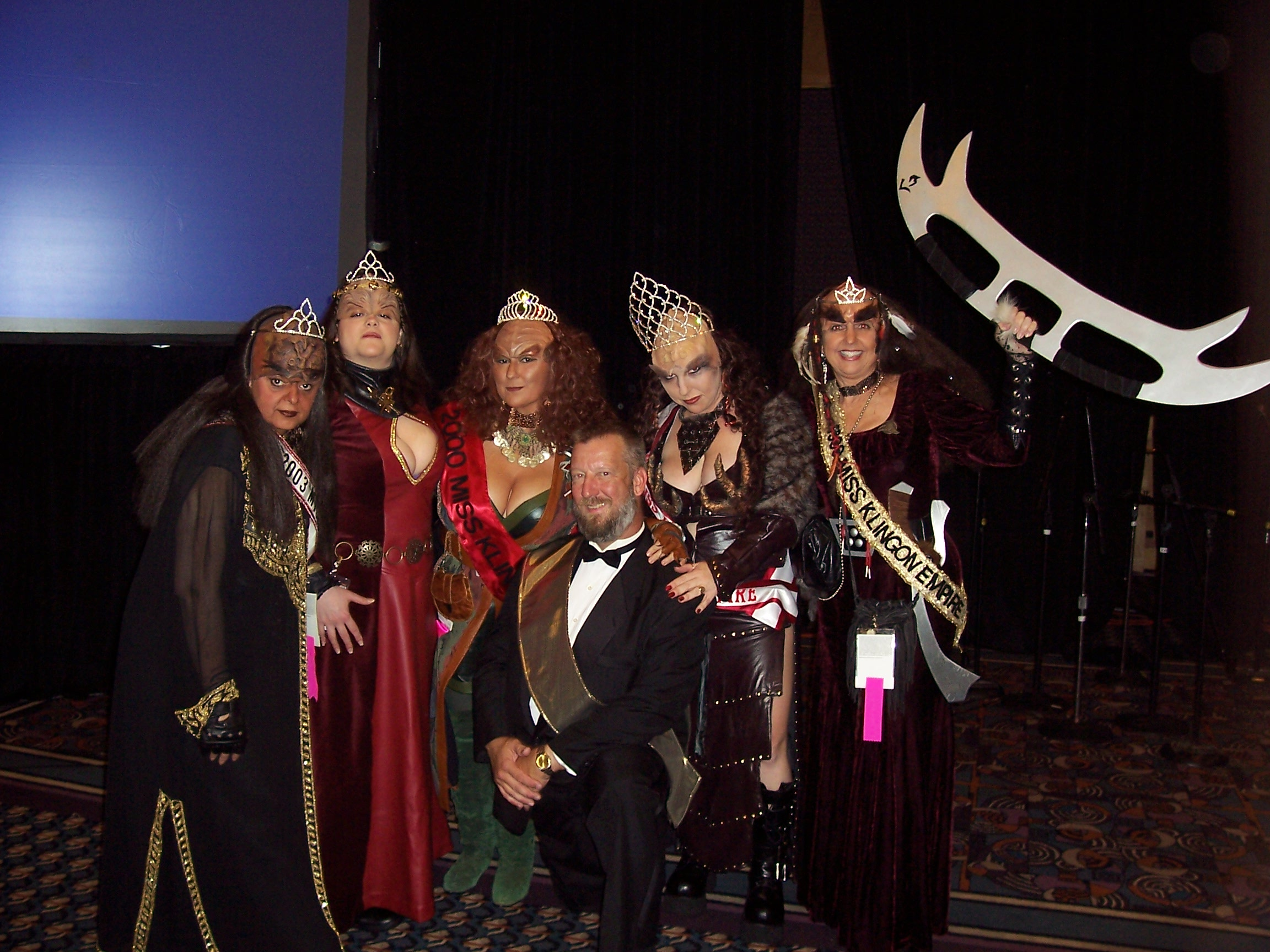 Four of the first five winners of the Miss Klingon Empire Beauty Pageant (1999-2004) return to bask in the glory of the 2005 pageant.  Created by Watts, the MKE pageant received a tremendous amount of media coverage in the mainstream press during its 11-year run at Dragon*Con, and will return as a highlight of TrekTrax Atlanta.